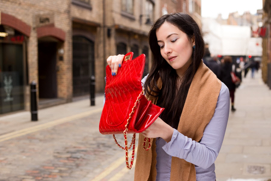 девушка открывает красную сумочку на улице западно-европейского города
