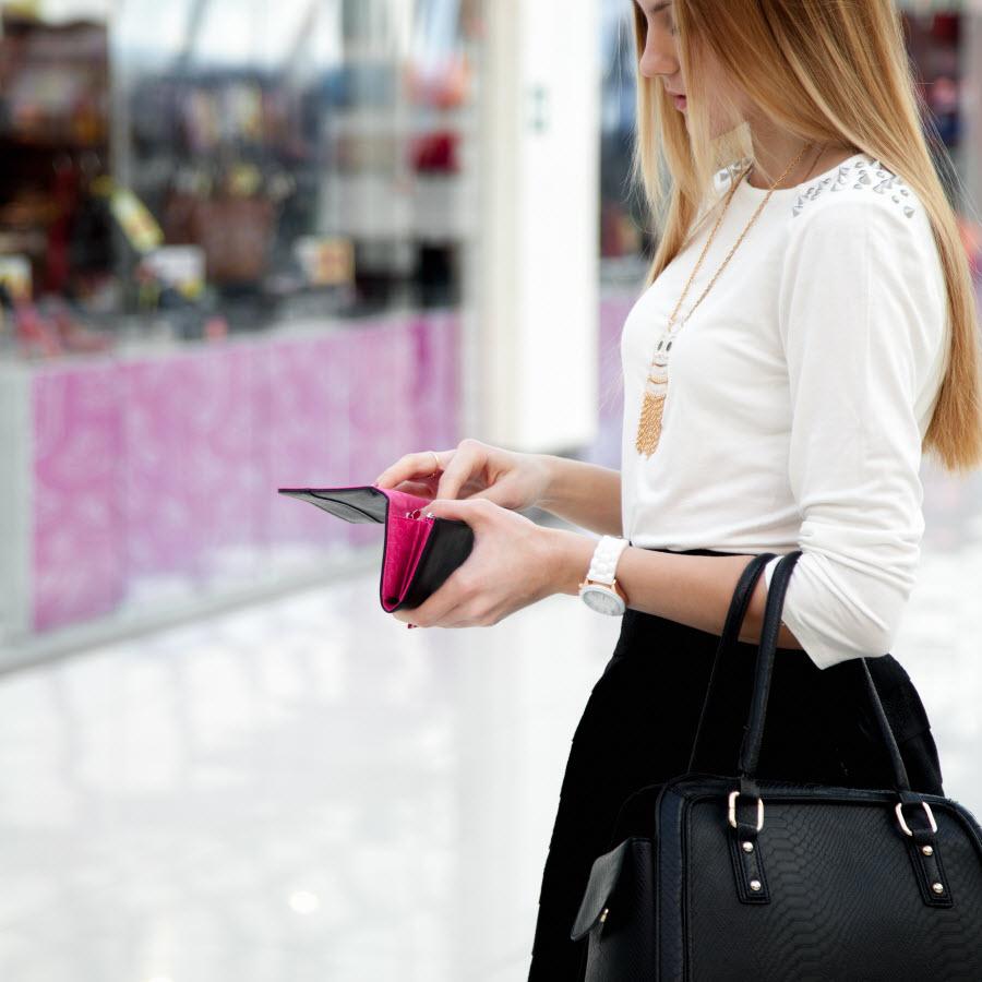 стильная девушка в торговом центре с сумкой в руках открывает кошелек
