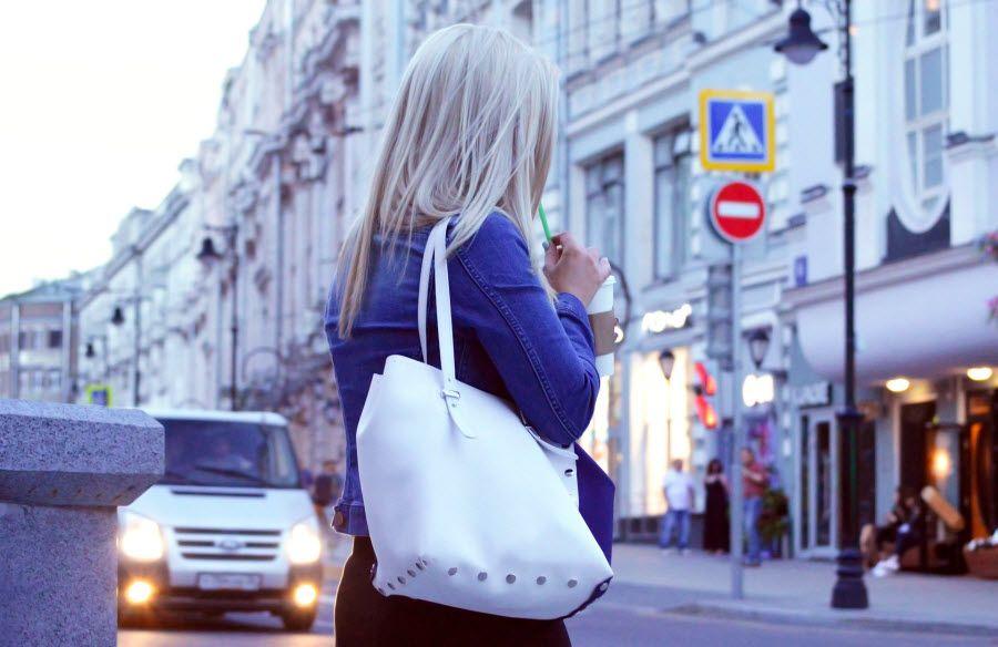 блондинка с белой сумкой на плече на улице российского города