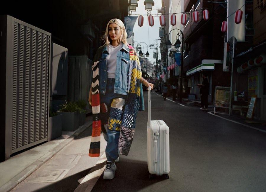 chica asiática con maleta Rimowa