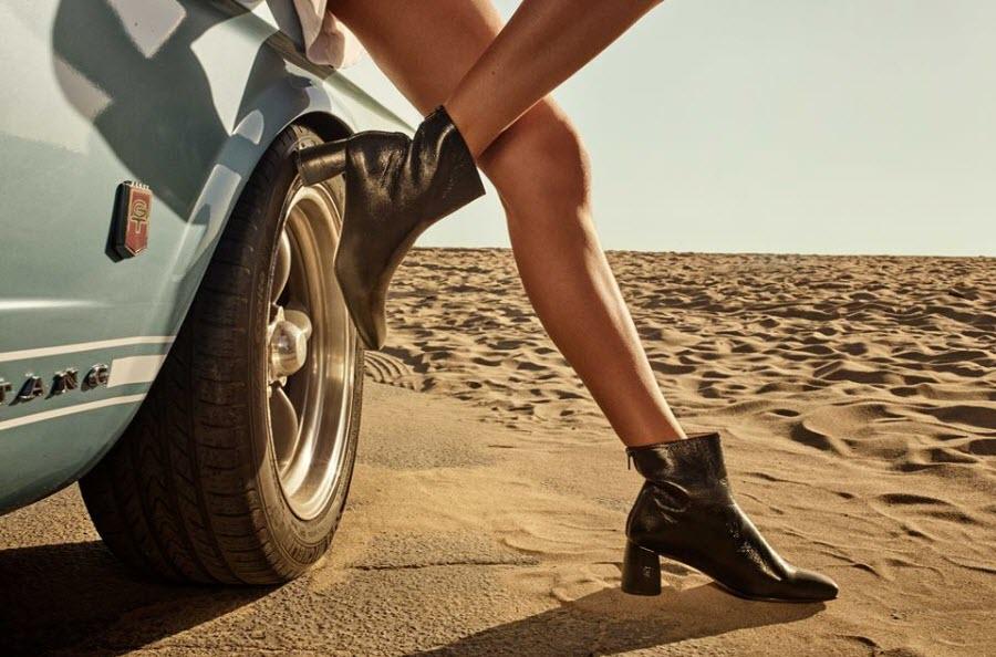 женские ноги в ботильона Stuart Weitzman на фоне пустыни и культовой машины Ford Mustang