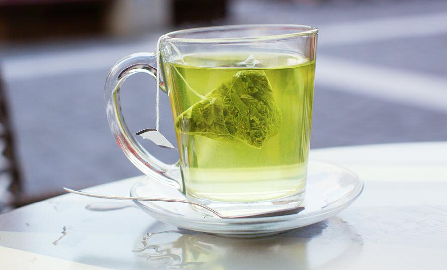 tách trà xanh nóng trên bàn trong quán cà phê ngoài trời